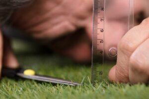 Pain in the grass? Image of man using a ruler to ensure his grass is level.